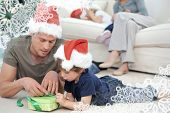 Father and son unwrapping a present lying on the floor against snowflake frame