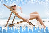 Gorgeous blonde sitting at the beach wearing sunhat and sunglasses against snow