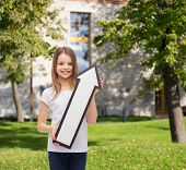 advertising, direction, summer vacation and childhood concept - smiling little girl with white blank arrow pointing up over campus background