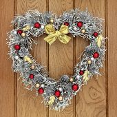 Heart shaped christmas wreath with red, gold and silver bauble decorations over old oak background.