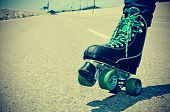 stock photo of roller-skating  - closeup of a young man roller skating on a no traffic road - JPG