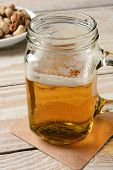 Closeup of a jar mug with beer. Vertical format on a rustic wood table and peanuts in the background.