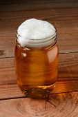 Glass of beer in a country bar setting served in a canning jar. Vertical format on a rustic wood background.