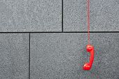 Red emercency call phone hanging down on a wall
