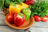 Composition with stuffed peppers on plate and fresh herbs, spices and vegetables, on wooden background