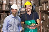 Warehouse manager and foreman smiling at camera in a large warehouse
