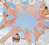 Volunteers with hands together against blue sky against snowflake frame