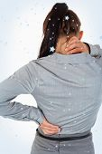 Portrait of the painful back of a young businesswoman against snow falling
