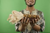 Midsection of man holding corn