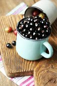 Ripe blackcurrants and gooseberries in mug on board, on wooden background.