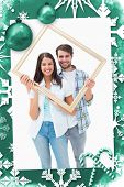 Happy young couple holding picture frame against christmas frame