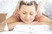 Relaxed woman enjoying a back massage against fir tree forest and snowflakes