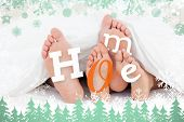 Composite image of pair of feet under duvet with home text against snow