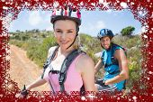 Fit couple cycling up mountain trail smiling at camera against snow