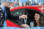 Composite image of customer receiving car keys against snow