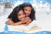 Mother and daughter reading book together on bed against snow