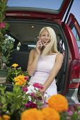 Woman Sitting By Flowers On Back Of Minivan Using Cell Phone