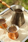 coffee preparation in copper pot with hot golden sand outdoor, shallow dof