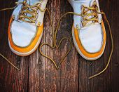 a pair of deck shoes on a nice wooden porch with the laces in a heart shape toned with a retro vintage instagram filter effect