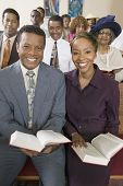 pic of pews  - Young couple with Bibles sitting on church pews portrait - JPG