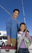 Father and daughter holding fishing poles outside RV