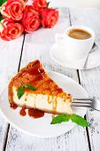 Cheese cake  in plate and tuft of roses on wooden background