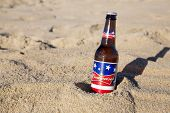 OLD ORCHARD BEACH, USA - September 03, 2014: A cold bottle of Budweiser in the sand on a hot, summer's day. Bud was introduced in 1876 and is a best seller in the United States.