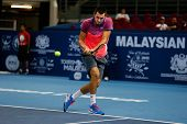 SEPTEMBER 23, 2014 - KUALA LUMPUR, MALAYSIA: Bernard Tomic of Australia makes a backhand return in his first round match at the Malaysian Open Tennis 2014 event. This is an ATP sanctioned tournament.