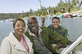Three generation family on fishing trip smiling (portrait)