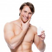 Young happy smiling man applying lotion on face - isolated on white.