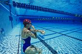 Female swimmer resting underwater in swimming pool