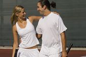 Mixed Doubles Partners standing on Court arms around