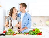 Cooking. Happy Couple Cooking Together - Man and Woman in their Kitchen at home Preparing Vegetable Salad.Diet. Dieting. Healthy Food concept. Dinner. Vegan food
