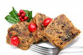 Slices of Christmas fruitcake isolated on white with holly garnish and fork.