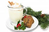 Holiday eggnog with fruitcake, isolated on white with holly and pine garnish.