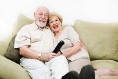 Senior couple relaxing at home enjoy watching television.