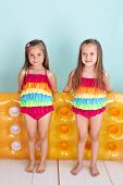 Group of children dressed in fashion swimsuits posing on aqua blue background