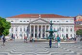 Lisbon, Portugal. August 31, 2014: Dona Maria II National Theatre, one of the fountains and the typical wave design in handmade cobblestone pavement in Dom Pedro IV Square, better known as Rossio