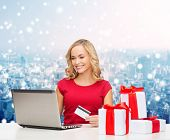 christmas, holidays, technology and shopping concept - smiling woman in red blank shirt with gift boxes, credit card and laptop computer over blue lights background