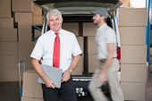 Warehouse manager smiling at camera with delivery in background in a large warehouse