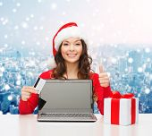 christmas, holidays, technology and shopping concept - smiling woman in santa helper hat with credit card, gift box and laptop computer showing thumbs up gesture over snowy city background