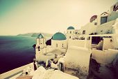 Oia town on Santorini island, Greece at sunset. Vintage, retro style. Traditional and famous churches with blue domes over the Caldera, Aegean sea