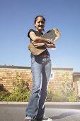 Teenage girl holding skateboard