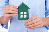 Woman hands holding paper house close up