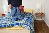 Boy standing on bed holding stuffed animal