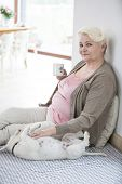 Portrait of happy senior woman having coffee while stroking dog at home