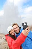 Iceland tourists selfie photo by Strokkur geyser. Couple happy visiting famous tourist attractions and landmarks on the Golden Circle. Multiracial travel couple on holiday vacation sightseeing.