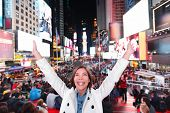 Happy excited woman in New York City, Manhattan, Times Square cheering celebrating joyful at night w
