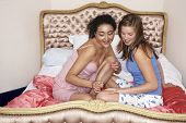 Teenage girl painting friend's fingernails on bed at slumber party poster