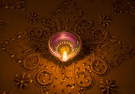 stock photo of dharma  - A traditional indian earthen lamp glowing on a golden luxurious embroidered background - JPG